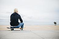 Spain, Torredembarra, back of young man sitting on his skateboard looking to the sea - JRFF000441