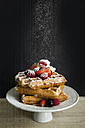 Cake stand of Belgian waffles with different berries sprinkled with icing sugar - VABF000152