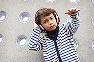 Portrait of little boy rapping while listening music with headphones - VABF000155
