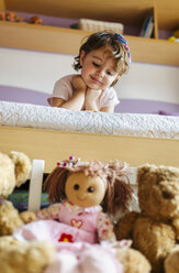 Portrait of little girl lying on bed looking at her toys in the foreground - MGOF001438