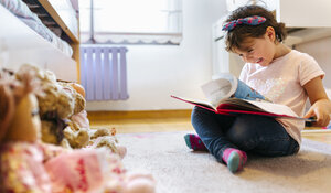 Laughing little girl sitting on the floor watching picture book - MGOF001441