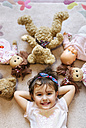 Portrait of smiling little girl lying on the floor with teddies and dolls around her - MGOF001444