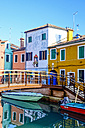 Italy, Veneto, Burano, view to colourful row of houses with footbridge in the foreground - HAMF000149