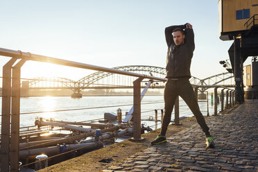 Germany, Cologne, Young man warming up for workout - MADF000801