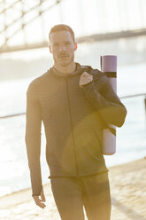 Germany, Cologne, Young man carrying yoga mat - MADF000807