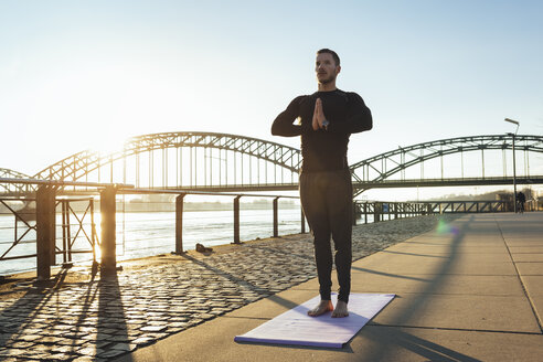 Germany, Cologne, Young man practicing yoga at the riverside - MADF000810