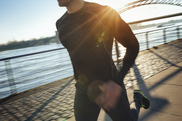 Germany, Cologne, Young man running at the riverside - MADF000813