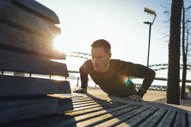 Germany, Cologne, Young man doing push ups on bench - MADF000816