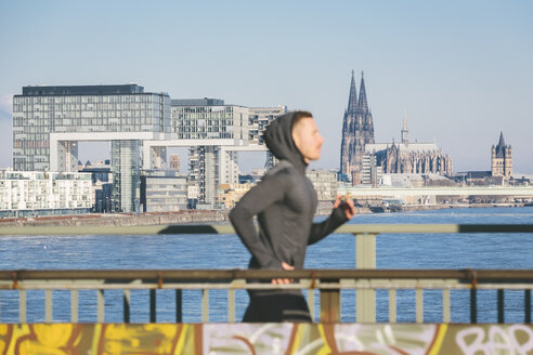 Germany, Cologne, Young man running at the riverside - MADF000819