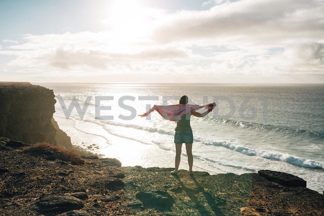 Spain, Fuerteventura, El Cotillo, back view of woman looking to the sea - GEMF000730