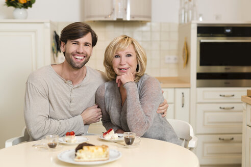 Portrait of happy mother and adult son sitting at table in the kitchen - SHKF000498