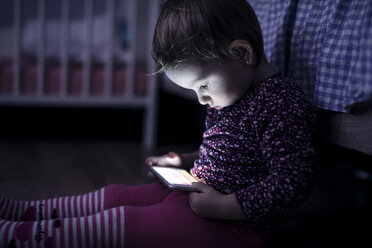 Toddler sitting on the floor playing with smartphone - HAPF000237