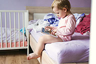 Toddler sitting on bed playing with digital tablet - HAPF000240