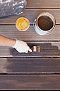 Woman's hand applying glaze with brush on floorboards - GWF004629