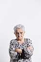 Portrait of angry senior woman in front of white background - RAEF000892
