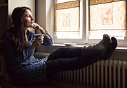 Daydreaming woman with feet on the heater drinking cup of tea while looking through window - OPF000108