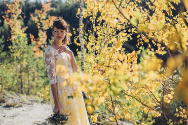 Portrait of young woman with bouquet in autumnal nature - MJF001714