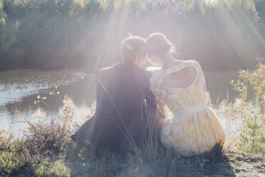 Back view of lovers sitting at water's edge - MJF001717