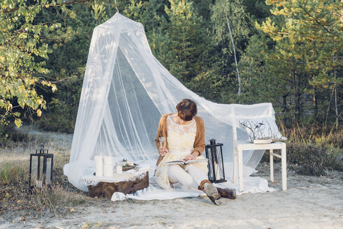 Woman reading a book in a romantic camp in autumnal nature - MJF001729