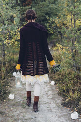 Back view of old-fashioned styled woman with storm lamp walking on a path - MJF001735