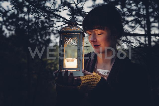 Portrait of woman with closed eyes holding storm lamp, - MJF001738 - Jana Mänz/Westend61