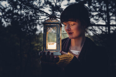 Portrait of woman with closed eyes holding storm lamp, - MJF001738