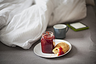 Digital tablet, cup of coffee and croissant with jam on bed - FMKF002277