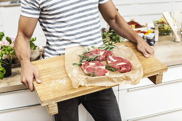 Man carrying wooden tray with steaks - FMKF002319