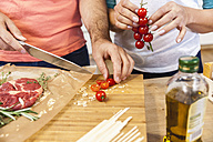 Slicing tomatoes on chopping board - FMKF002322