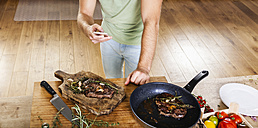 Man with prepared steaks in kitchen using celll phone - FMKF002334
