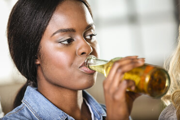Young woman drinking bottle of beer - FMKF002337