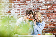 Happy young couple in kitchen eating watermelon together - FMKF002340