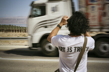 Israel, man taking picture at the roadside while truck is passing by - REAF000056