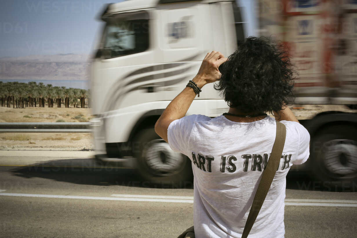 Israel, man taking picture at the roadside while truck is passing by - REAF000056 - realitybites/Westend61