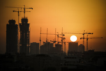 Israel, Tel Aviv, cityscape with cranes at sunset - REAF000077