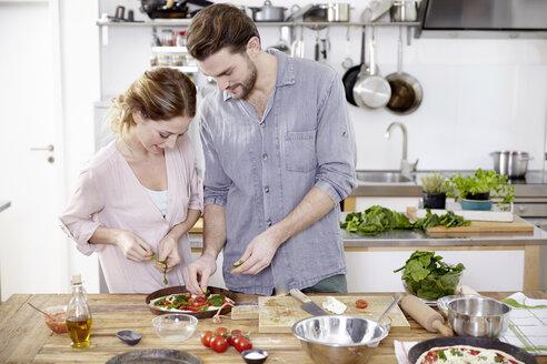 Couple preparing pizza in kitchen - FMKF002346