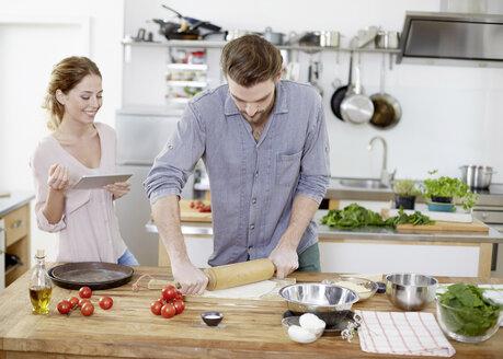 Couple preparing pizza dough in kitchen - FMKF002355