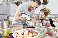 Couple in kitchen pouring sugar into bowl - FMKF002385