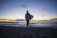 Spain, Barcelona, surfer at sunrise on the beach - SKCF000063
