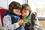 Two little boys sitting in a bus playing with smartphone - VABF000171