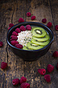 Bowl of kiwi apple rocket smoothie with chia seed, popped amarant, kiwi slices and raspberries - LVF004554