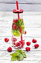 Glass bottle of infused water with raspberries and mint - LVF004557