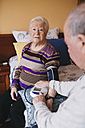 Senior man checking blood pressure of his wife at home - GEMF000742