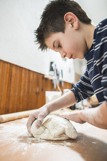 Boy kneading dough on kitchen worktop - DEGF000655