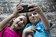 Portrait of brother and little sister talking a selfie with smartphone - SARF002581