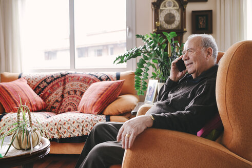 Portrait of smiling senior man telephoning with smartphone at home - GEMF000748