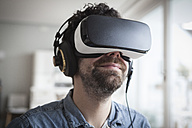 Smiling man wearing Virtual Reality Glasses and headphones - RBF004090