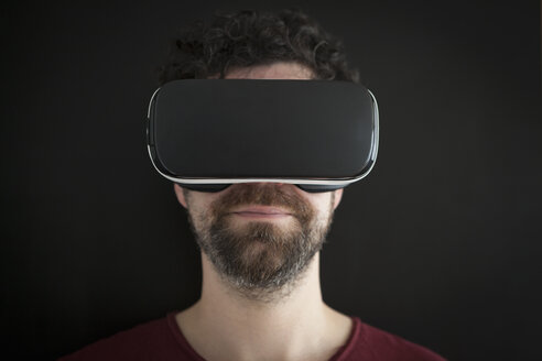 Man wearing Virtual Reality Glasses in front of black background - RBF004096