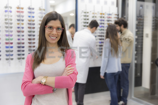 Portrait of smiling woman in an optician shop with people in background - ERLF000140 - Enrique Ramos/Westend61
