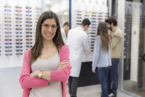 Portrait of smiling woman in an optician shop with people in background - ERLF000140